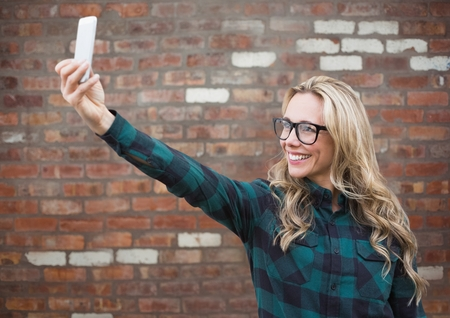 Digital composite of Millennial woman taking selfie against red brick wall