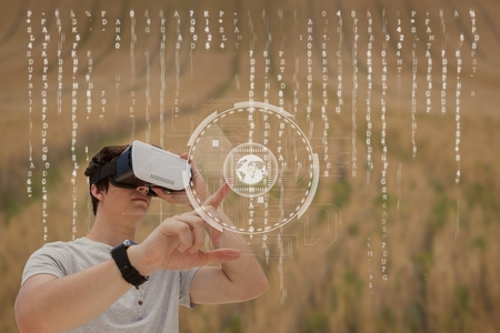 Digital composite of Man in VR headset touching interface against field background with interface Stock Photo