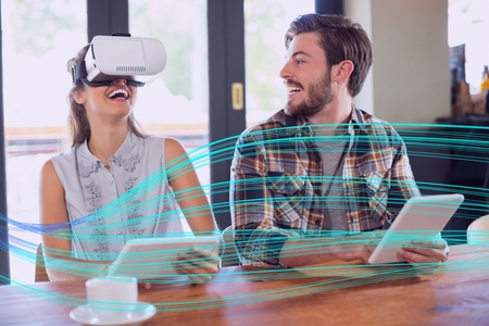 Digital composite of Woman in VR headset and man smiling behind light interface Stock Photo