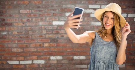 Digital composite of Millennial woman in summer clothes taking selfie against red brick wall