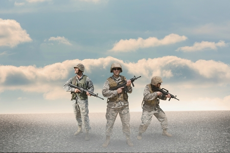 Digital composite of Soldier men holding weapons against desert background Stock Photo