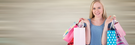 Digital composite of Shopper holding up bags against blurry brown background