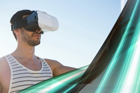 Digital composite of Man in VR headset touching green light interface