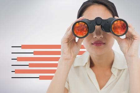 Compuesto digital de la mujer mirando a través de binoculares contra el fondo blanco con infografías Foto de archivo - 82269303