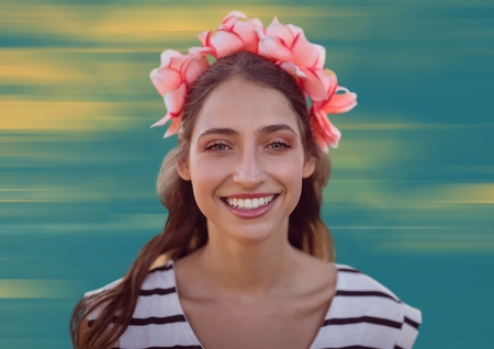 Digital composite of Close up of woman with flowers in hair against blurry yellow and blue background Stock Photo