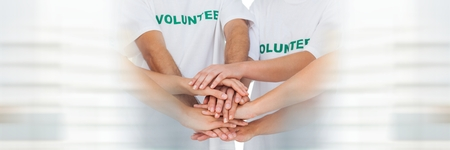 Digital composite of Close up of volunteer team putting hands together and blurry white framing