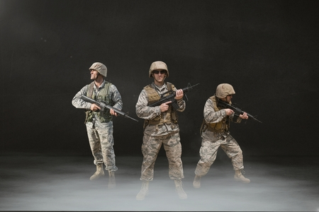 Digital composite of Soldier men holding weapons against black background