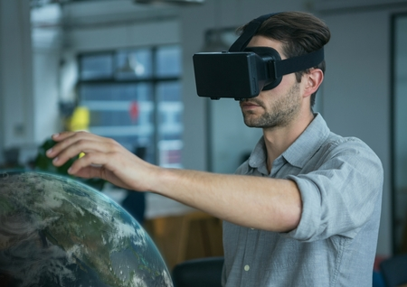smart man: Digital composite of Man in VR headset touching a 3D planet