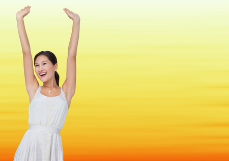 Digital composite of Woman in white dress celebrating against blurry yellow background