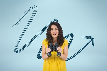 Digital composite of Happy woman with binoculars against blue background with arrow Stock Photo