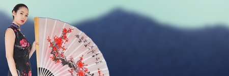 Digital composite of Geisha and giant fan against blurry mountain
