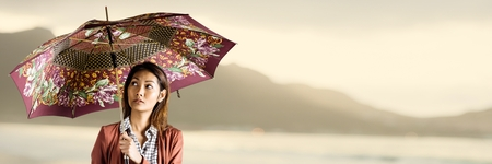 Digital composite of Millennial woman with patterned umbrella against blurry yellow coastline Stock Photo