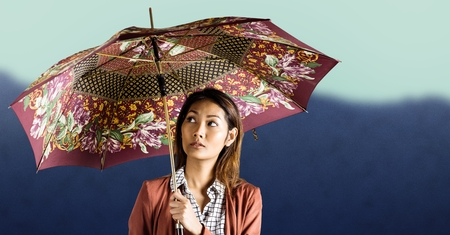 Digital composite of Millennial woman with patterned umbrella against blurry mountain
