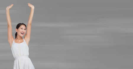 Digital composite of Woman in white dress celebrating against blurry grey background Stock Photo