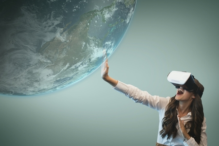 Digital composite of Surprised woman in VR headset touching 3D planet against blue background