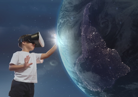sphere standing: Digital composite of Boy in VR headset touching 3D planet against sky background Stock Photo