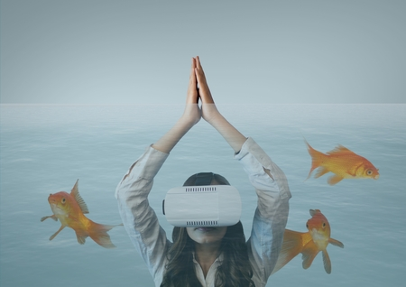 Digital composite of Woman in VR headset diving with fishes Stock Photo
