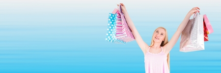 Digital composite of Shopper with bags in air against blurry blue background