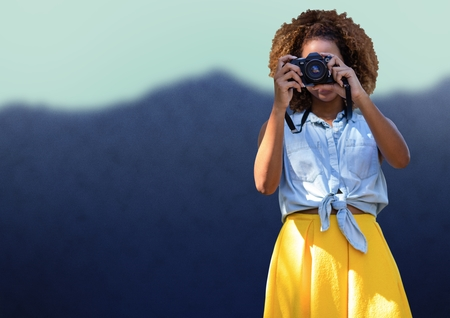 Digital composite of Millennial woman in summer clothes with camera against blurry mountain