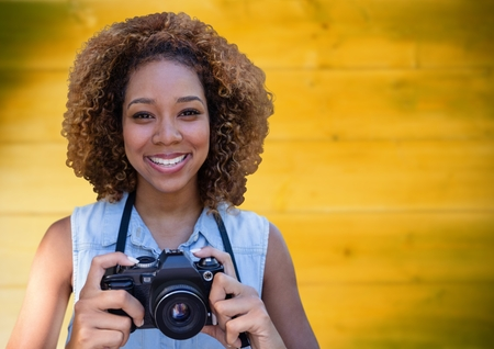 Digital composite of Close up of millennial woman with camera against blurry yellow wood panel