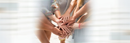 Digital composite of Hands together on beach and blurry white framing