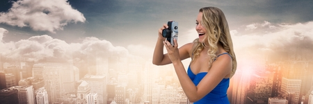 man made: Digital composite of Millennial woman  with camera against skyline with clouds