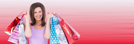 Digital composite of Shopper holding up bags against blurry red background Stock Photo