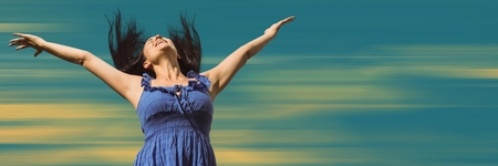 Digital composite of Woman in wind with arms out against blurry yellow and blue background Stock Photo