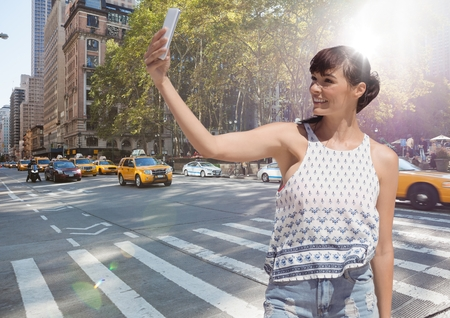 Digital composite of Millennial girl in summer clothes taking selfie against street with flare