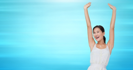 Digital composite of Woman in white dress celebrating against blurry blue background
