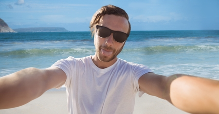 Digital composite of Millennial man taking selfie and sticking out tongue against beach Stock Photo