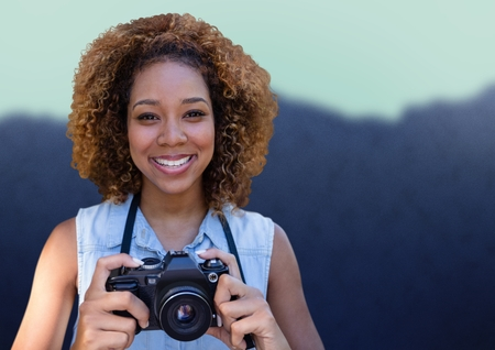 Digital composite of Millennial woman with camera against blurry mountain