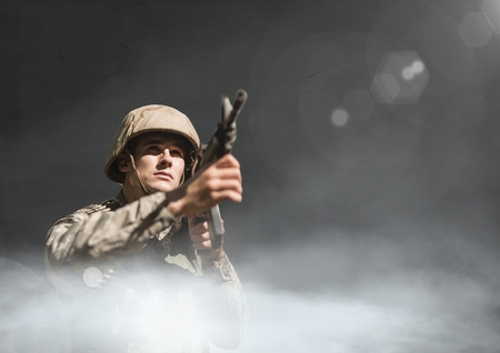 worn out: Digital composite of Soldier man holding a weapon against black background with clouds and flares Stock Photo