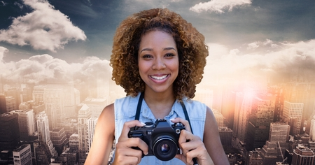 Digital composite of Close up of millennial woman with camera against skyline with clouds Stock Photo