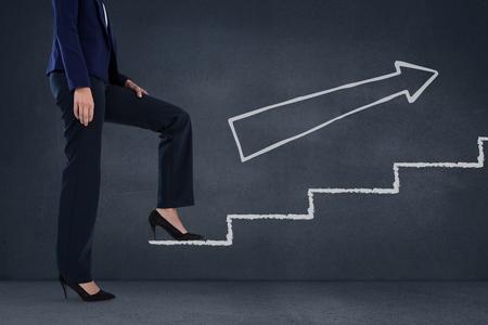 白い矢印で青い背景に階段を登る女性実業家のデジタル合成
