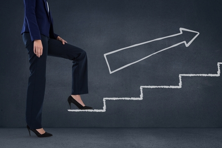 trouser: Digital composite of Business woman climbing stairs against blue background with white arrow Stock Photo
