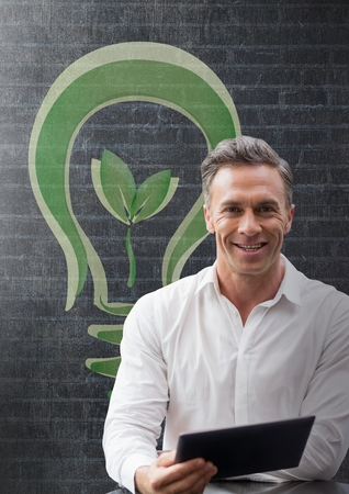 energy work: Digital composite of Happy business man at a desk using a tablet against black wall with green graphic