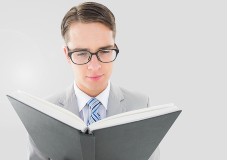 Digital composite of Portrait of Man reading book with grey background Stock Photo