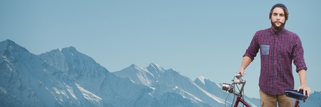 Digital composite of Millennial man with bicycle against mountain tops