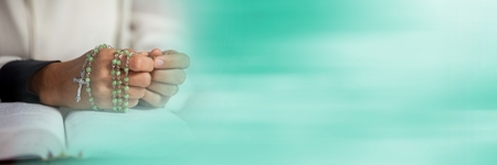 Digital composite of Hands with rosary on bible and blurry teal transition