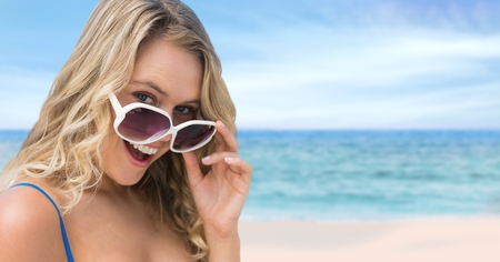 Digital composite of Woman at the beach holding sunglasses