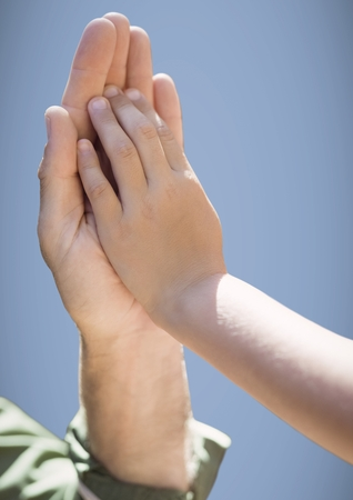 Digital composite of Close up of father and child high five against purple background