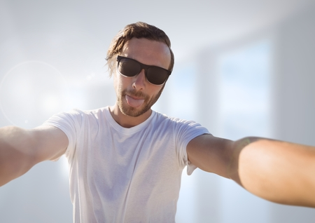 resting: Digital composite of man taking casual selfie photo in front of blurred background Stock Photo