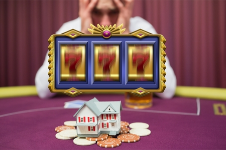 Digital composite of Casino slots spinning with worried man gambling his house in the background