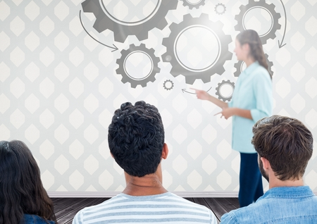 floorboards: Digital composite of Group of people in front of cog wheel graphics and woman speaker Stock Photo