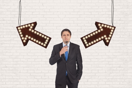 dubious: Digital composite of Confused business man standing against white wall with arrows