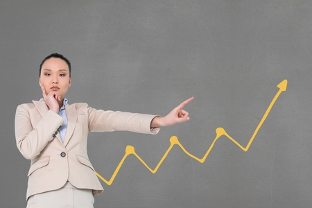 well dressed woman: Digital composite of Business woman pointing to the rich against grey background with yellow arrow