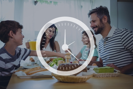 jag: Digital composite of Clock icon against family having dinner photo Stock Photo