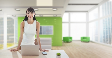 Digital composite of Happy business woman at a desk using a computer