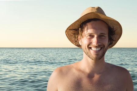Digital composite of Man at the beach smiling